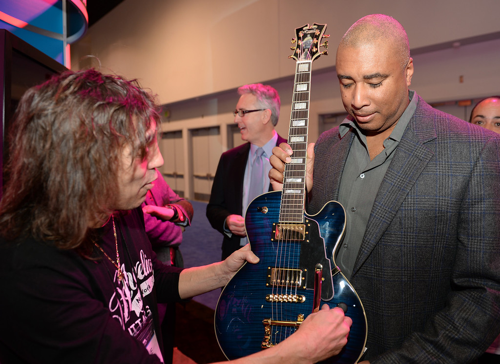 Description of . Former New York Yankee Bernie Williams, right receives his custom made guitar from Steve Pisani, left, from D'Angelico Guitars during the Media Preview event for the NAMM Show at the Anaheim Convention Center on Wednesday January 22, 2014. The NAMM Show, National Association of Music Merchants, is a trade-only event for the music products industry that is held every January. It is one of the two largest music product trade shows in the world. (Staff Photo by Keith Durflinger/San Gabriel Valley Tribune)