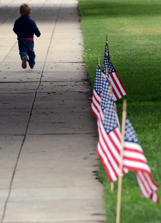 Description of . Jason Mabon Jr., 2 runs past a row of flags during a memorial service for fallen service members Friday May 17, 2013 in front of the Memorial Chapel at the University of Redlands. Mabon's father, Jason Mabon, is an Air Force Reservist attending the university. The ceremony featured a special tribute to Keith Taylor, a University of Redlands alumnus and father of a University of Redlands student. He was killed serving in Iraq. (Rick Sforza/Staff photographer, Redlands Daily Facts)