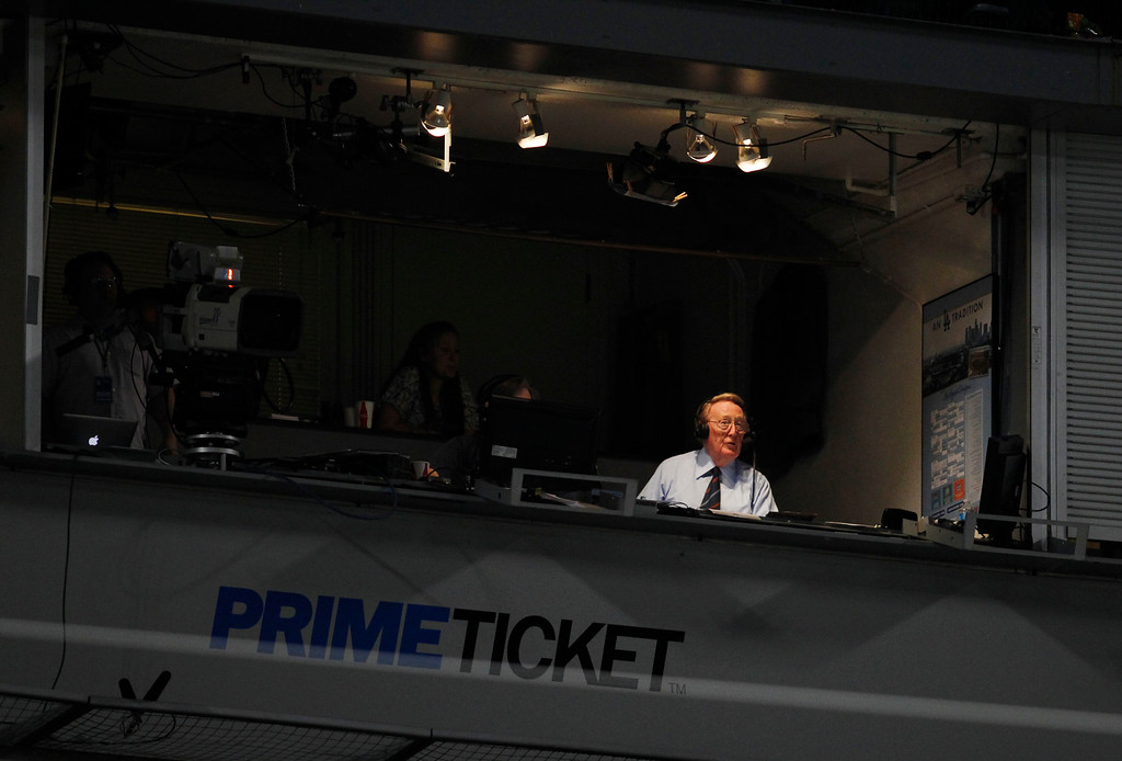 Description of . Sportscaster Vin Scully broadcasts from a press box booth at Dodger Stadium during the MLB exhibition baseball game between the Los Angeles Angels and Los Angeles Dodgers Tuesday, April 3, 2012, in Los Angeles. (AP Photo/Danny Moloshok)