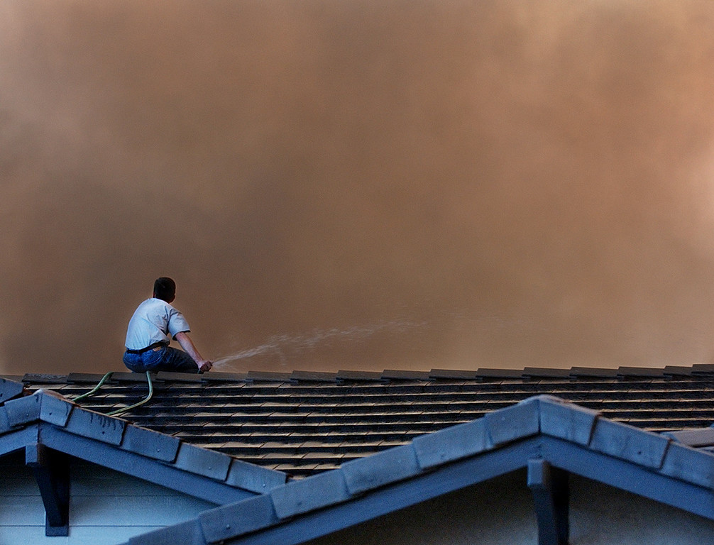 Description of . The GrandPrix fire started three days before the Old Fire.  It fed into the Old Fire. Ten years later, there are rumblings that it too was started by an arsonist. But to this day, its origins remain a mystery. A Rancho Cucamonga resident hoses down his roof as flames approach his home near the top of  Etiwanda Avenue Friday morning October 24, 2003.  (Staff photo by Will Lester/Inland Valley Daily Bulletin)