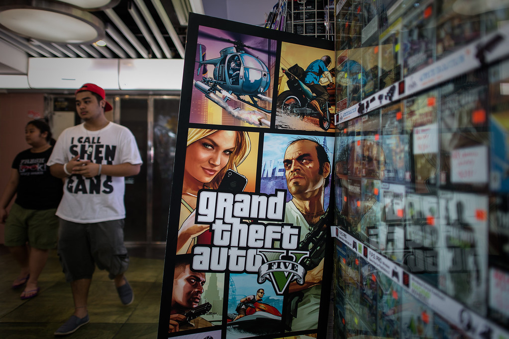 """Description of . A man walks past a billboard of the \""""Grand Theft Auto V\"""" video game in Hong Kong on September 17, 2013. The game hit the streets in the former British colony as it launched worldwide on September 17, 2013 in respective time zones.     (PHILIPPE LOPEZ/AFP/Getty Images)"""