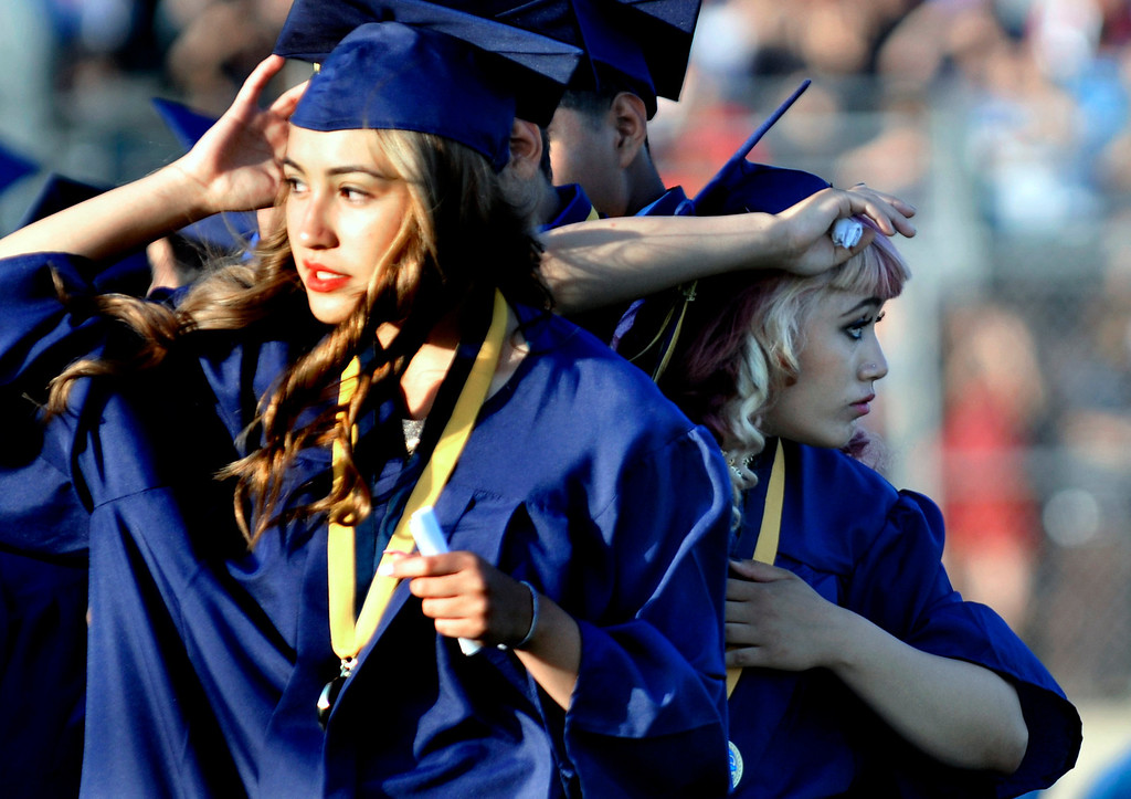 Description of . Norma Rubio, left, and Flor (cq) Rosa look for family and friends.   South El Monte High School Graduation on their football stadium, Wednesday, June 11,  2014.  (Mike Mullen photo)