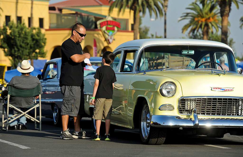 Description of . Yucaipa resident Albert Tellez and his seven-year-old son Diego, stand by their '55 Chevy at the Rendezvous Back to Route 66 event at San Manuel Stadium in San Bernardino on Friday, Sept. 20, 2013. (Photo by Rachel Luna / San Bernardino Sun)