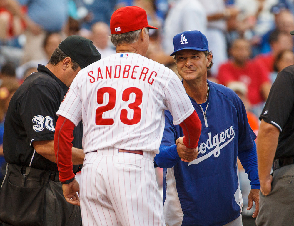 Description of . Los Angeles Dodgers manager Don Mattingly, right, shakes hands with Philadelphia Phillies interim manager Ryne Sandberg as they hand in their line-up cards before  a baseball game on Friday, Aug. 16, 2013, in Philadelphia. (AP Photo/Christopher Szagola)