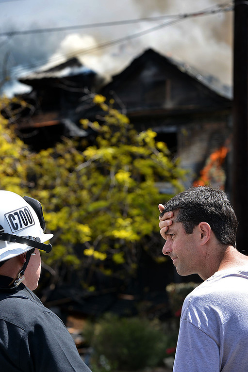 Description of . Tim McNaughton, right, speaks with Jeff Frazier, Chief of the Redlands Fire Department, as firefighters work to extinguish a fire burning McNaughton's home. The home in the 1600 block of Olive Street, one of the city's historic neighborhoods, was destroyed in a fire Wednesday April 9, 2014, according to fire officials. As they arrived, firefighters found the home, built in 1903, engulfed in flames and smoke billowing out of the structure. (Photo by Rick Sforza/The Sun)