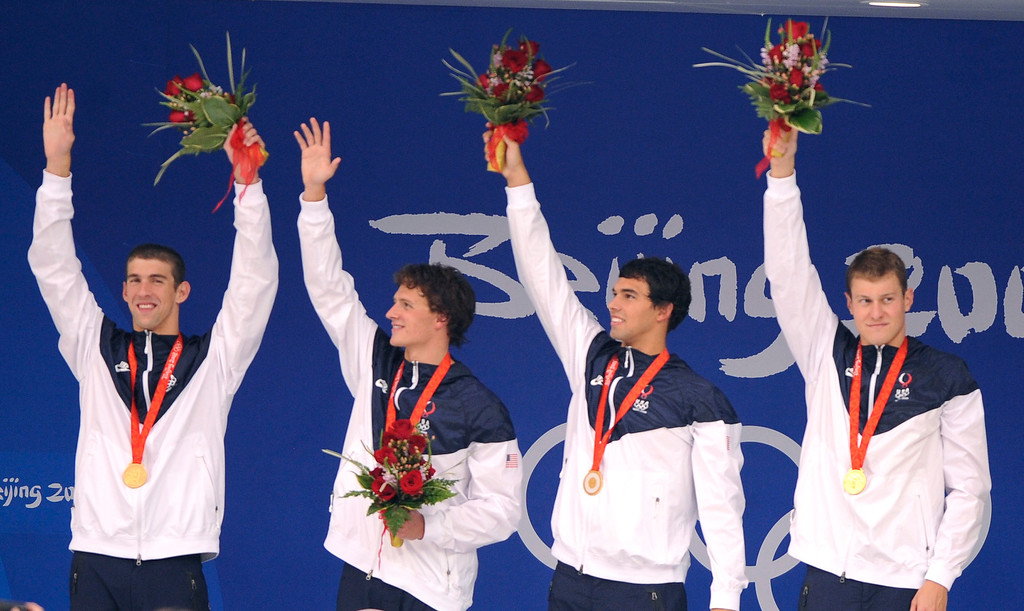 Description of . U.S. men's 4x200-meter freestyle relay team members, from left, Michael Phelps, Ryan Lochte, Ricky Berens and Peter Vanderkaay wave with their medals  during an awarding ceremony after setting a world record to win the swimming competition in the National Aquatics Center at the Beijing 2008 Olympics in Beijing, Wednesday, Aug. 13, 2008. (AP Photo/Mark J. Terrill)