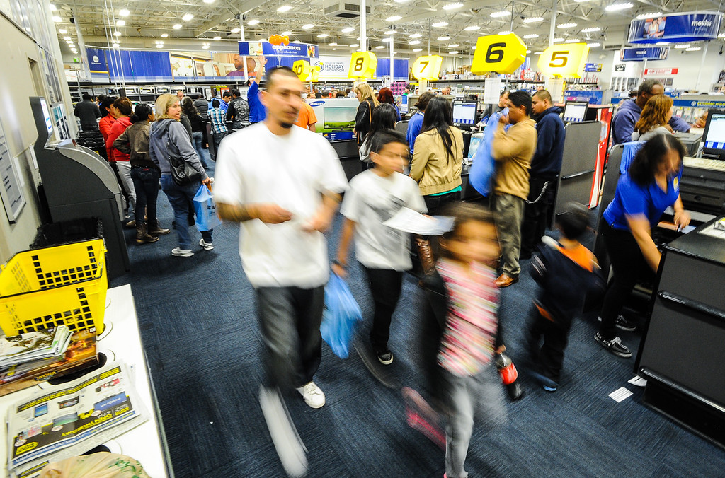 Description of . Shoppers buy items at Best Buy after the store opened its doors at 6 p.m. for early Black Friday sales on Thanksgiving in San Bernardino on Thursday, Nov. 28, 2013. Many retail stores pushed the boundary the Black Friday tradition this year with offering Black Friday deals on Thanksgiving day. (Photo by Rachel Luna / San Bernardino Sun)