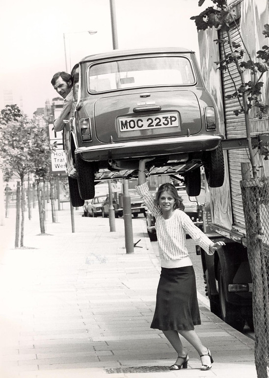 Description of . American actress Lindsay Wagner appears to hold a man in a Mini above her head during a visit to Britain to promote the television series 'The Bionic Woman,' London, England, June 7, 1976. The car was actually hoisted by a care, which was out of sight of the camera. Wagner is teaching Acting and Directing for Television and Film and Motion Picture Production as an adjunct faculty member at San Bernardino Valley College. (Photo by Express Newspapers/Getty Images)