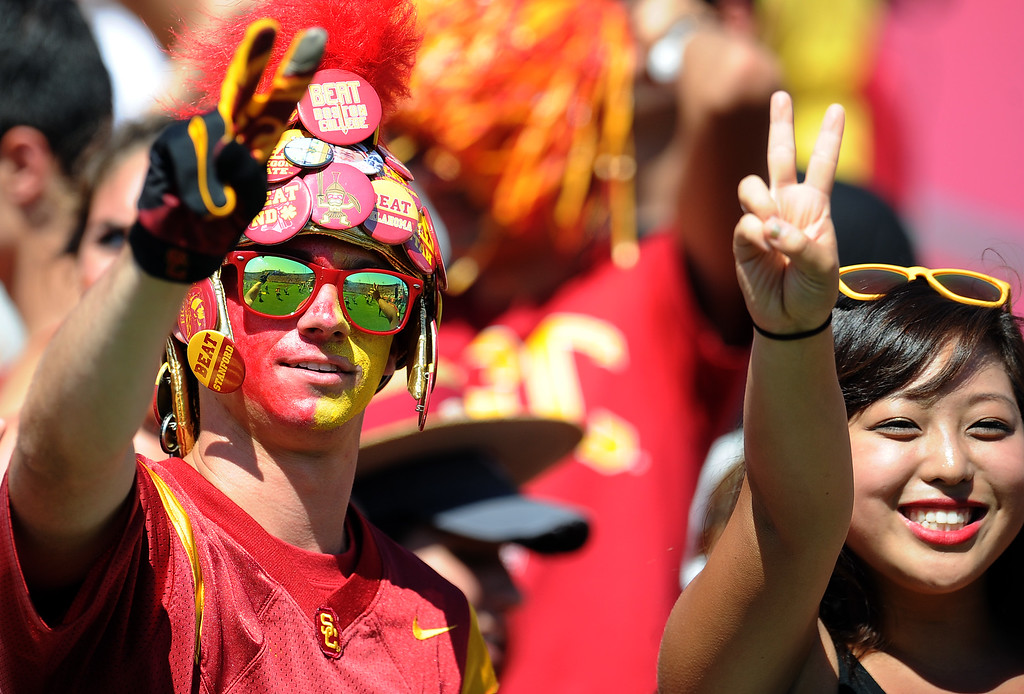 Description of . Southern California fans cheer during the second half of an NCAA college football game against Boston College in the Los Angeles Memorial Coliseum in Los Angeles, on Saturday, Sept. 14, 2013. Southern California won 35-7. 