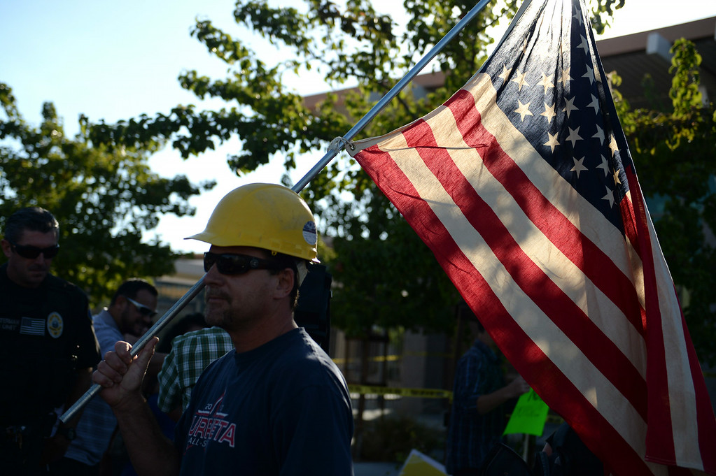 Description of . Construction worker Paul Hathaway, of Murrieta, holds an american flag outside a town hall meeting on Wednesday, July 2, 2014 at Murrieta Mesa High School in Murrieta, Ca. The meeting is being held in response to immigrants who were being processed through a Texas Border Patrol Station and delivered to the Murrieta Border Patrol Station on Tuesday, which created protests from both sides of the immigration issue. (Micah Escamilla/The Sun)