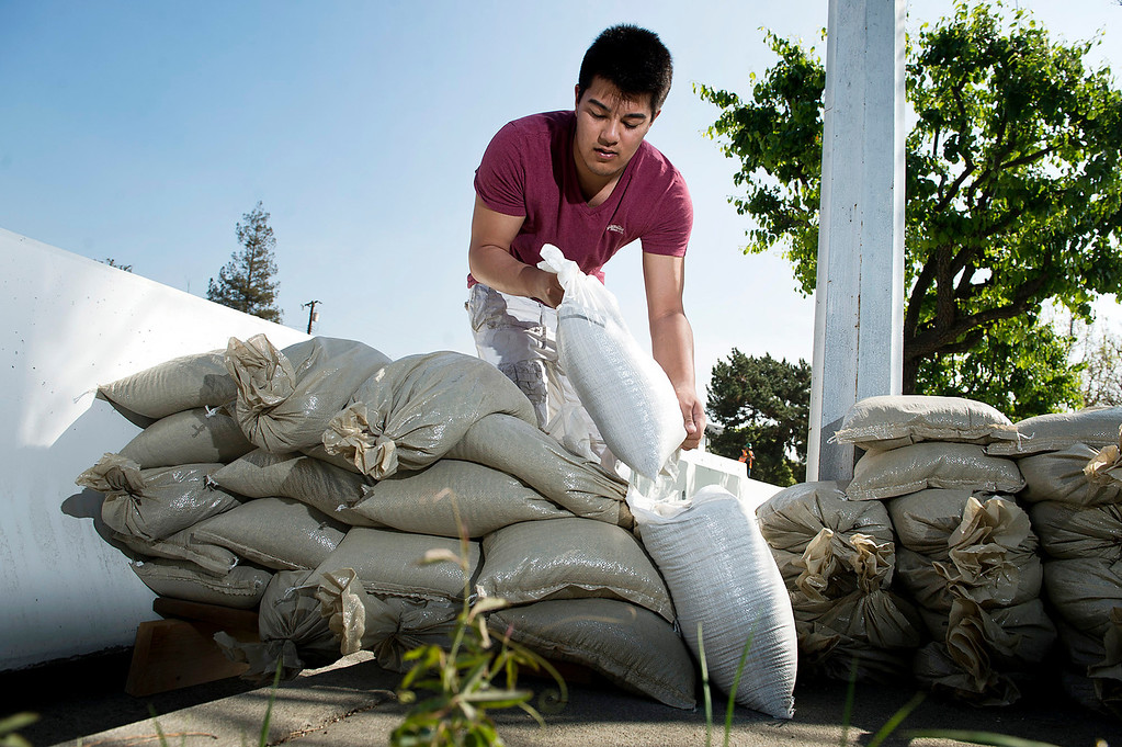 Description of . Chris Romero, 17, helps his neighbors stack sandbags along the 800 block of Rainbow Drive in Glendora on Tuesday, Feb. 25, 2014. The city of Glendora is preparing for two major rainstorms that will hit the region this week that potentially will cause mudslides in the area devastated by the Colby Fire. (Photo by Watchara Phomicinda/ San Gabriel Valley)