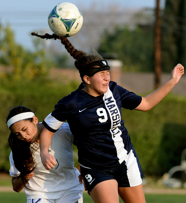 Description of . Marshall's Sandy Martinez (9) goes up for the header as her pony tail swings through the arias Bishop Amat's Jamie Peters defends in the first half of a prep soccer match at Bishop Amat High School in La Puente, Calif., on Thursday, Jan. 9, 2014.Amat won 3-0. (Keith Birmingham Pasadena Star-News)
