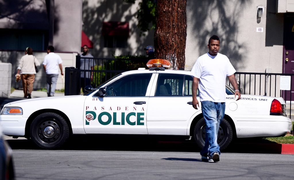 Description of . People walk in and out of Kings Village in Pasadena as Pasadena Police investigate an officer involved shooting at the Pasadena apartment complex Friday, October 11, 2013. (Photo by Sarah Reingewirtz/Pasadena-Star News)