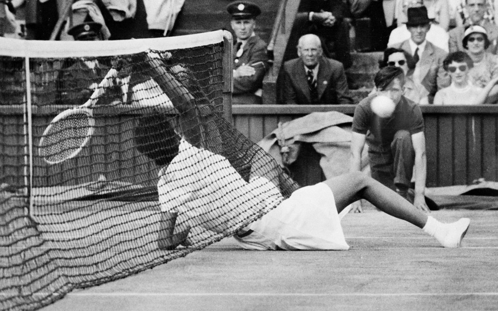 Description of . Althea Gibson, of New York City, slides under the net to return the ball during semi-finals of the women\'s doubles at the All-England Lawn Tennis Club in Wimbledon, England, July 6, 1956.  Britain\'s Angela Buxton and Gibson defeated Louis Brough, of Beverly Hills, Ca., and Shirley Fry of St. Petersburg, Fla., 7-5, 6-4.  (AP Photo)