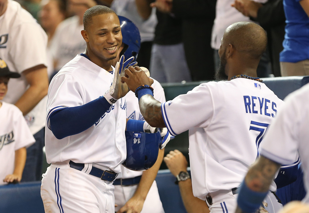 Description of . TORONTO, CANADA - SEPTEMBER 11: Moises Sierra #14 of the Toronto Blue Jays is congratulated by Jose Reyes #7 after scoring a run in the fourth inning after hitting a triple during MLB game action against the Los Angeles Angels of Anaheim on September 11, 2013 at Rogers Centre in Toronto, Ontario, Canada. (Photo by Tom Szczerbowski/Getty Images)
