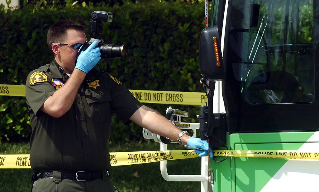Description of . Mike Russ, a San Bernardino Sheriff's crime scene investigator, takes photos of an OmniTrans bus that was struck by gunfire during an officer involved shooting in San Bernardino May 9, 2013. Two suspects in a Yucca Valley homicide led authorities on a high-speed chase Thursday that ended with a gun battle, one suspect dead, another wounded and a California Highway Patrol officer wounded. The CHP didn't say where the bullet struck the officer, but said the wound was not life-threatening. (Rick Sforza/The Sun, San Bernardino)