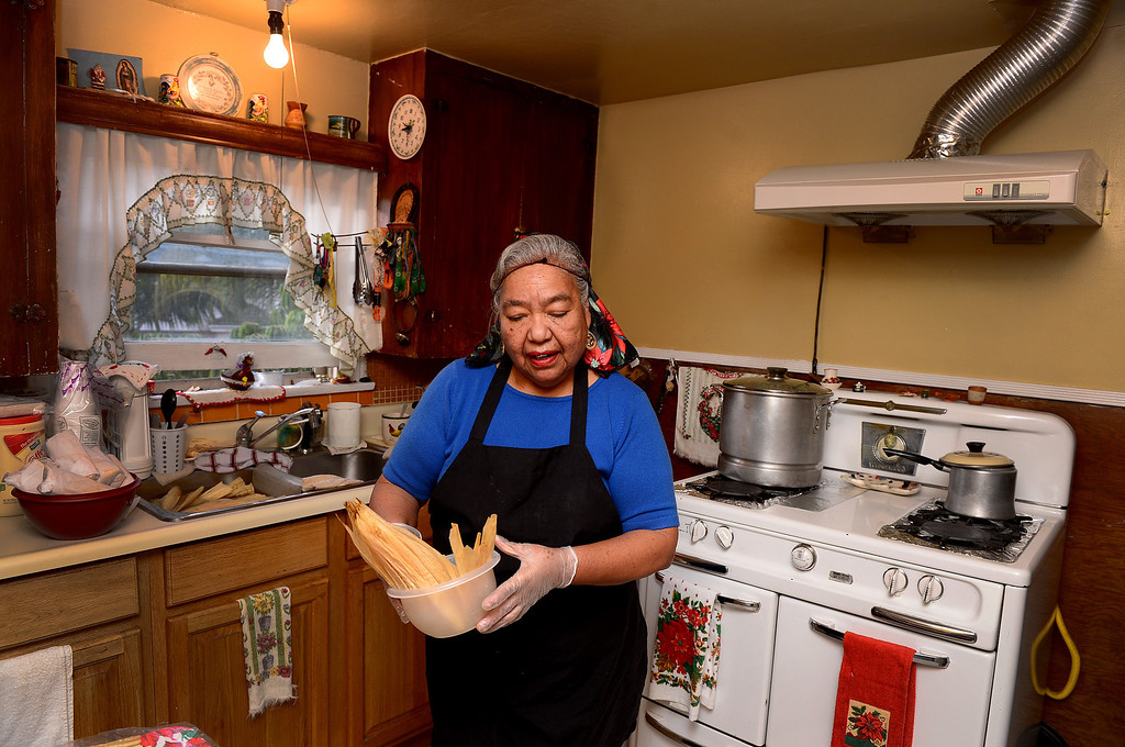 Description of . Santos Garza, 68, prepares corn husks as she makes Christmas tamales for friends and family Saturday, December 21, 2013 in her Rosemead home that she shares with her 83-year-old husband Emede. Garza expects to make 18 dozen chicken, cheese and pork tamales this year. Tamales are a Christmas Eve tradition in Mexico. (Photo by Sarah Reingewirtz/Pasadena Star-News)