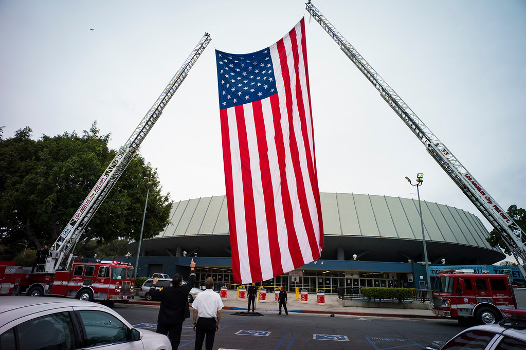 Description of . A giant US flag at the memorial for slain TSA officer Gerardo Hernandez at the Los Angeles Sports Arena Tuesday, November 12, 2013.  A public memorial was held for Officer Hernandez who was killed at LAX when a gunman entered terminal 3 and opened fire with a semi-automatic rifle.  ( Photo by David Crane/Los Angeles Daily News )