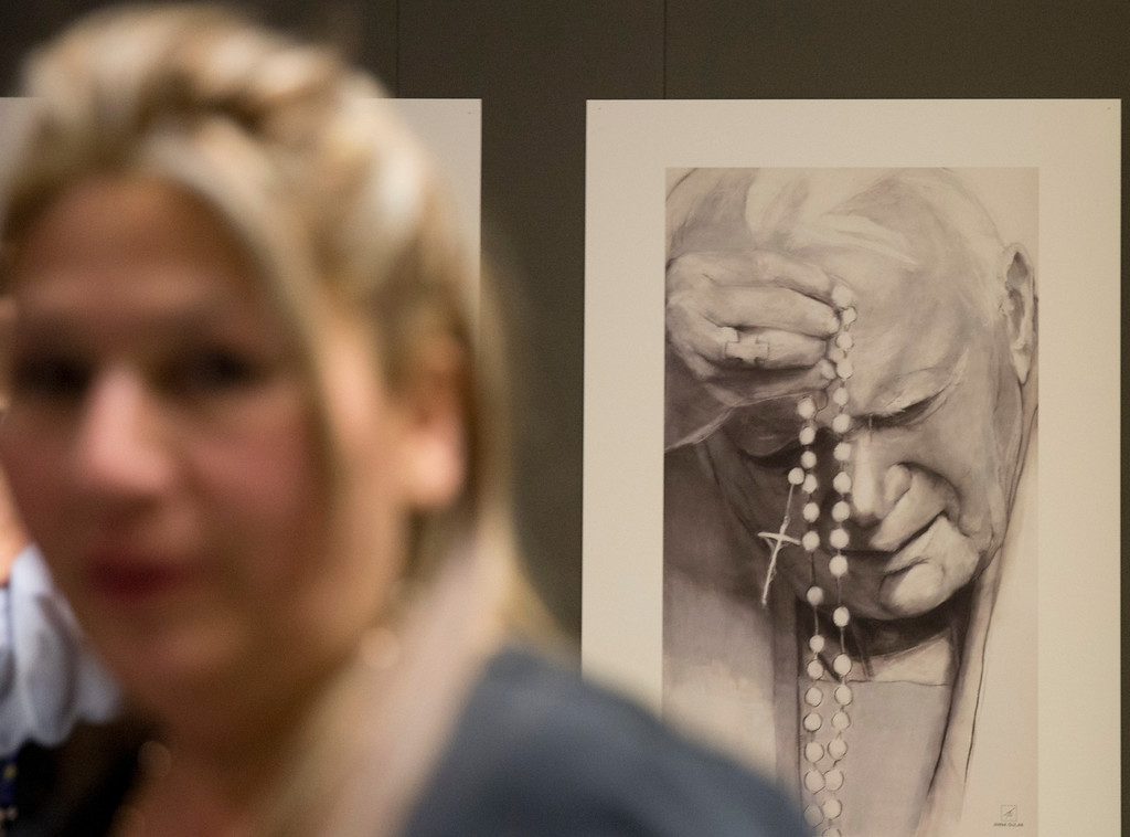 Description of . Floribeth Mora, a  Costa Rican woman whose inoperable brain aneurysm purportedly disappeared after she prayed to John Paul II, walks past a portrait of him made by Polish artist Anna Gulak as she leaves after a press conference at the Vatican, Thursday, April 24, 2014. John Paul II will be made saint together with late pope John XXIII during a solemn ceremony at the Vatican Sunday   (AP Photo/Alessandra Tarantino)