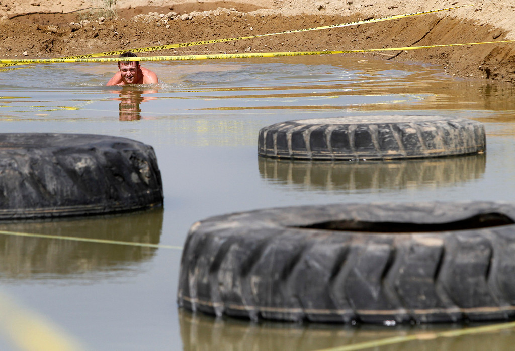 Description of . A runner makes his way thru a mud pit during the Sheriff's Athletic Federation's annual 5K Mud Run on Saturday, May 17, 2014 at the Sheriff's Department Academy in Devore, Ca. (Photo by Micah Escamilla/San Bernardino Sun)