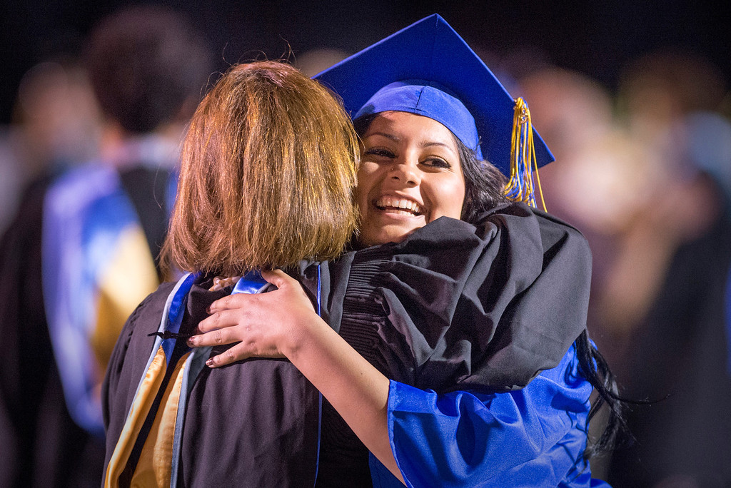 Description of . Jennifer Mata hugs one of her teachers after receiving her diploma during California High graduation at their Whittier campus stadium June 13, 2013.   (SGVN staff photo by Leo Jarzomb)