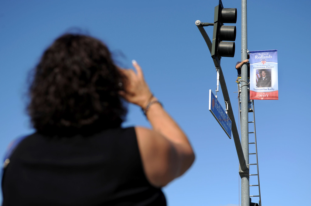 Description of . (John Valenzuela/Staff Photographer) Kathy Venegas takes a photo as Redlands Evening Kiwanis Club member Jerry Linkhart hangs a Hometown Heroes banner of her niece, Naval officer Samantha Kelly, at the corner of New Jersey St. and Redlands Blvd., Tuesday, August 27, 2013. Kelly is a E-5 Air Traffic Controller stationed in San Diego, an is a 2006 Redlands East Valley grad.