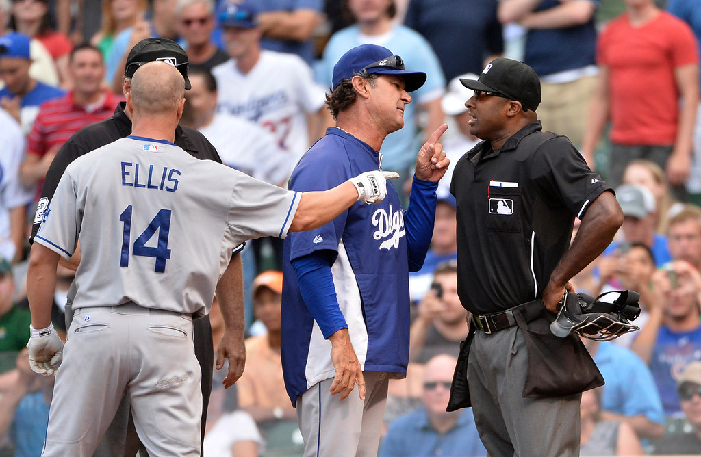 Description of . Manager Don Mattingly #8 of the Los Angeles Dodgers (C) talks with home plate umpire Alan Porter (R) after Porter ejected Mark Ellis #14 for arguing balls and strikes during the fourth inning against the Chicago Cubs at Wrigley Field on August 2, 2013 in Chicago, Illinois. Porter also ejected Mattingly. Dodgers won 6-2.   (Photo by Brian Kersey/Getty Images)