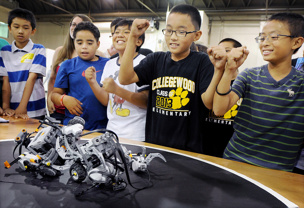 Description of . Cal Poly Pomona's Robotics Initiative invited 200 elementary and middle school students to a Robot Expo at LA Fairplex in Pomona Monday, May 20, 2013.  William Go, third from left, Nathan Leung, and Tyler Xu of Collegewood Elementary from Walnut Valley, cheering for their teams robot named