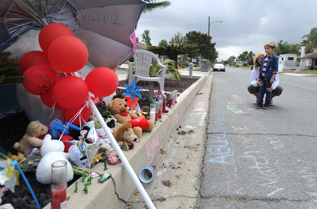 Description of . Cathy Hamilton and her grandson Judah of Rancho Cucamonga, visit the memorial site for Ryan Cruz Saldana, 3, who was hit by a truck and killed Friday, on Alta Loma Drive, May 7, 2014. (Photo by John Valenzuela/Inland Valley Daily Bulletin)