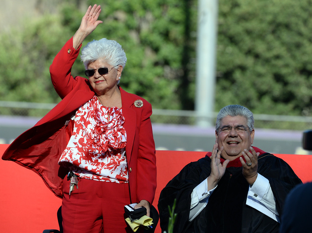 Description of . Grace Napolitano, U.S. Representative for California's 32nd congressional district waves to students as Dr. Ralph Pacheco looks on during the Whittier High School graduation at Whittier College in Whittier, Calif., on Wednesday, June 4, 2014.  (Keith Birmingham/Pasadena Star-News)