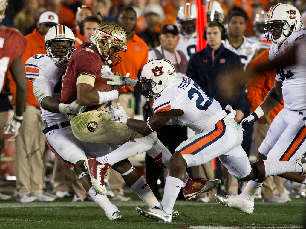 Description of . Florida's Jamies Winston (5) is tackle by Auburn's Anthony Swain (43) and Jonathan Ford (23) in the first half during the BCS National Championship game at the Rose Bowl in Pasadena Calif. on Monday, Jan. 6, 2014. (Watchara Phomicinda/ Pasadena Star-News)
