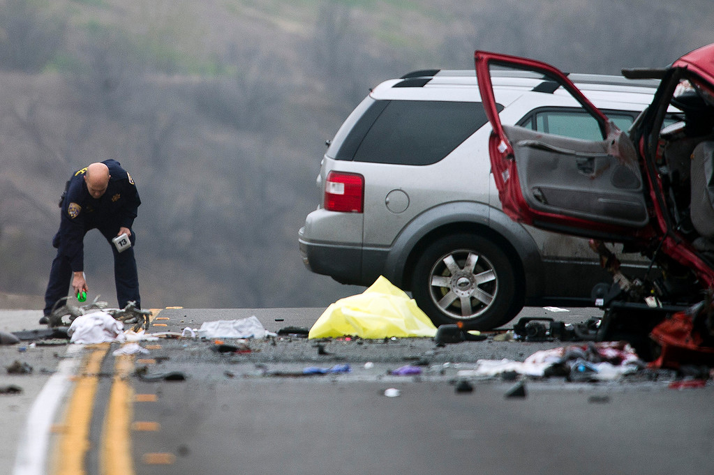 Description of . Officials investigate the scene of a three car accident where 6 people were killed on the westbound 60 Freeway near Philips Ranch Road in Diamond Bar, Calif. on Sunday morning, Feb. 9, 2013. The driver of the red Chevy Camaro was heading the wrong way when it collided head-on with a Ford Explorer. (Photo by Watchara Phomicinda/ San Gabriel Valley Tribune)