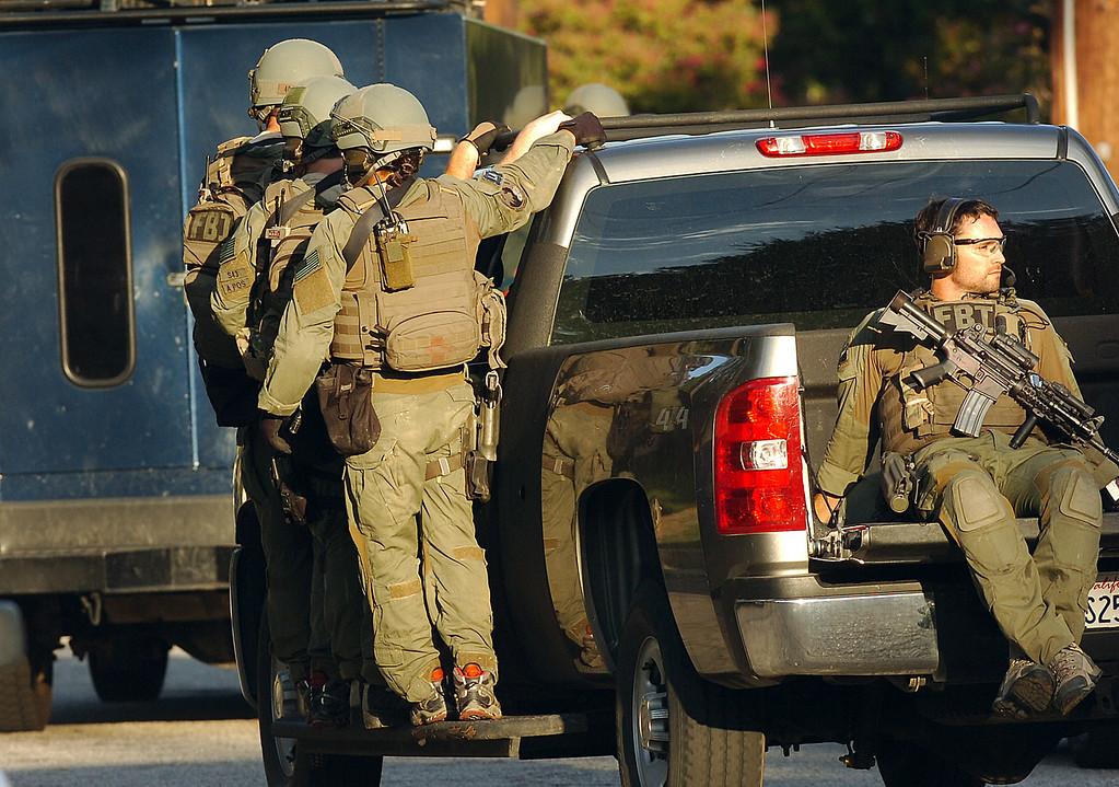 Description of . More than a dozen federal agents in body armor and other law enforcement officers raided a Redlands home Thursday morning as part of a gang investigation. The FBI gathered in the city at 5:12 a.m. and served a search warrant at a home in the 800 block of East High Avenue. Police took a man into custody at another location in the 400 block of Western Avenue in the city. (Staff photo by Rick Sforza)