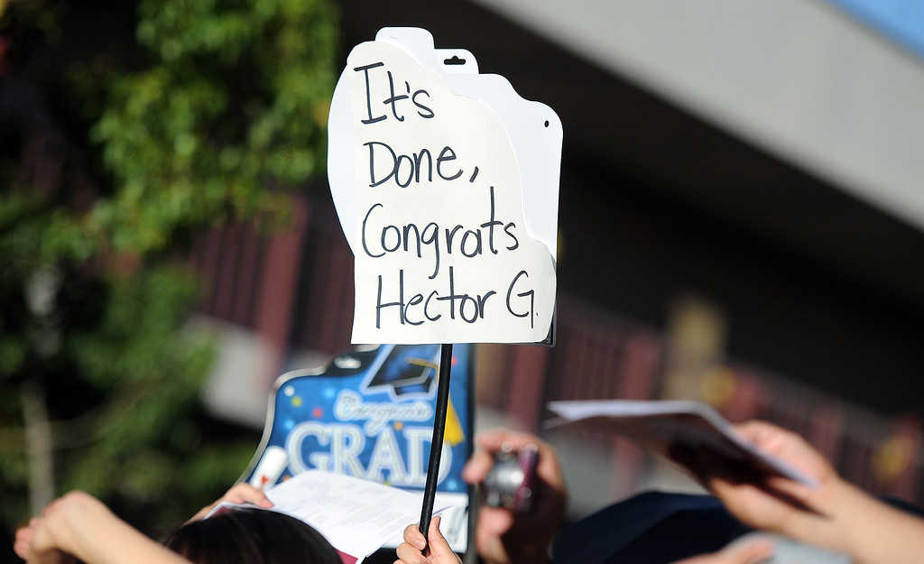 Description of . Family and friends hold signs during the Vail High School commencement at Vail High School on Tuesday, June 18, 2013 in Montebello, Calif.