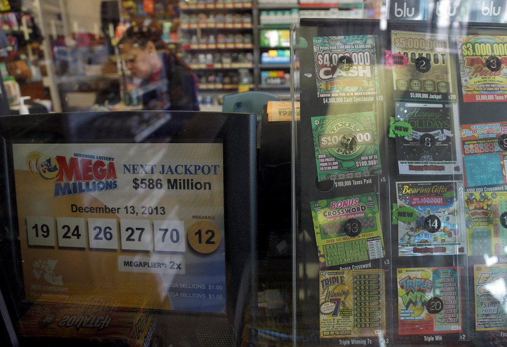 Description of . Anita Watson works behind a counter at Energy Express convenience store selling Mega Millions lottery tickets Monday, Dec. 16, 2013, in St. Louis. The Mega Millions jackpot now stands at an estimated $586 million with the next drawing set for Tuesday night. (AP Photo/Jeff Roberson)