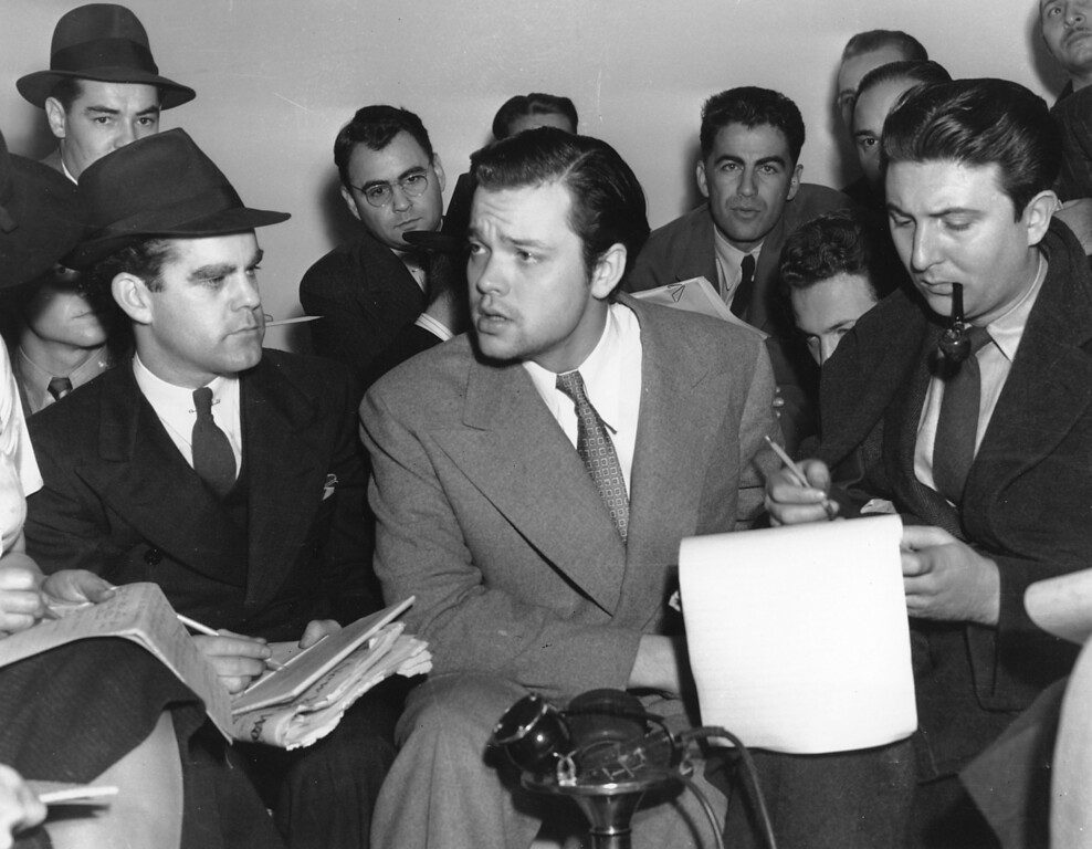 Description of . Orson Welles, center, explains to reporters on Oct. 31, 1938 his radio dramatization of H.G. Wells'