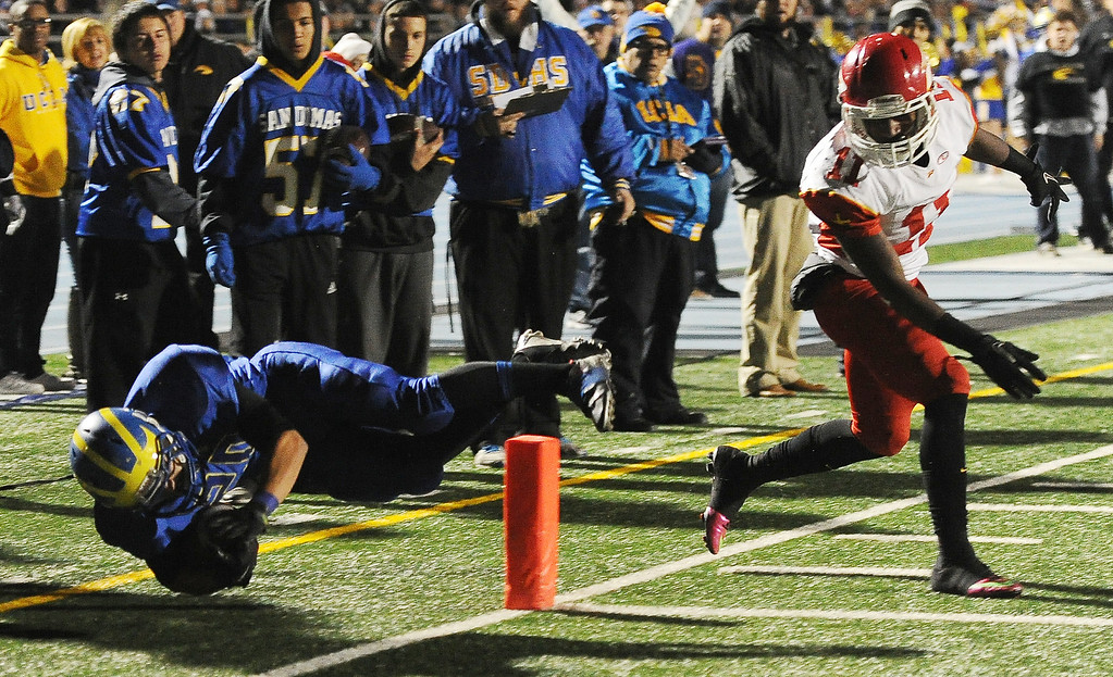 Description of . San Dimas' Manny Elizalde (20) dives for the touchdown past Paraclete's Melquise Stovall in the first half of a CIF-SS Mid-Valley Division championship football game at San Dimas High School in San Dimas, Calif., on Friday, Dec. 6, 2013.   (Keith Birmingham Pasadena Star-News)