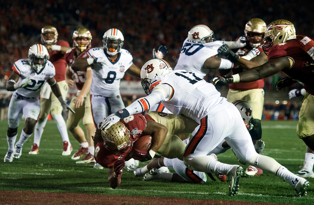 Description of . Timmy Jernigan (8) of Florida State scores a touchdown over Ben Durand (17) of Auburn in the first half during the BCS National Championship game at the Rose Bowl in Pasadena Calif. on Monday, Jan. 6, 2014. (Watchara Phomicinda/ Pasadena Star-News)