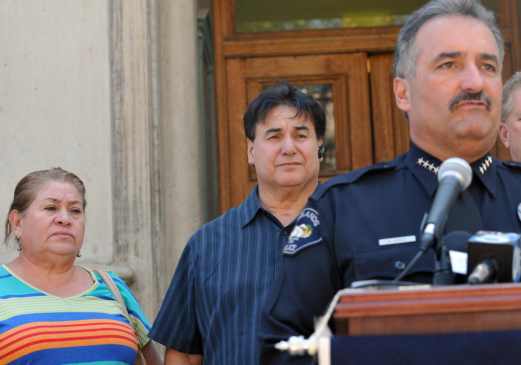 Description of . (John Valenzuela/Staff Photographer) Redlands Police Chief Mark Garcia gives an update in the murder investigation of Sylvia Flores, as her parents Sylvia and Robert Flores listen, during a press conference outside the police annex in Redlands, CA.Tuesday, September 12, 2013. Flores, a 23-year-old woman from Perris, CA. who's body was found in a orange groves near Citrus Plaza shopping center in Redlands.
