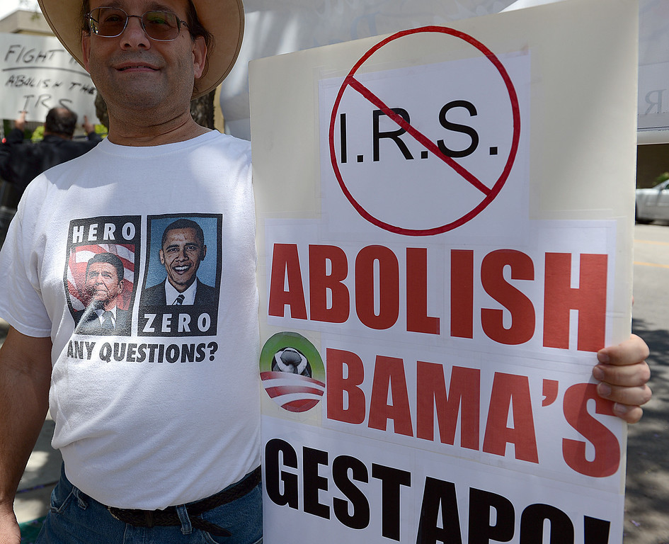 Description of . Michael Geradi, 54, of Menifee joined Tea Party members for a rally in front of the San Bernardino IRS Tuesday May 21, 2013 in response to the ongoing revelations related to the IRS targeting conservative groups for special attention. The Tea Party Patriots called for protests nationwide. (Rick Sforza/The Sun, San Bernardino)