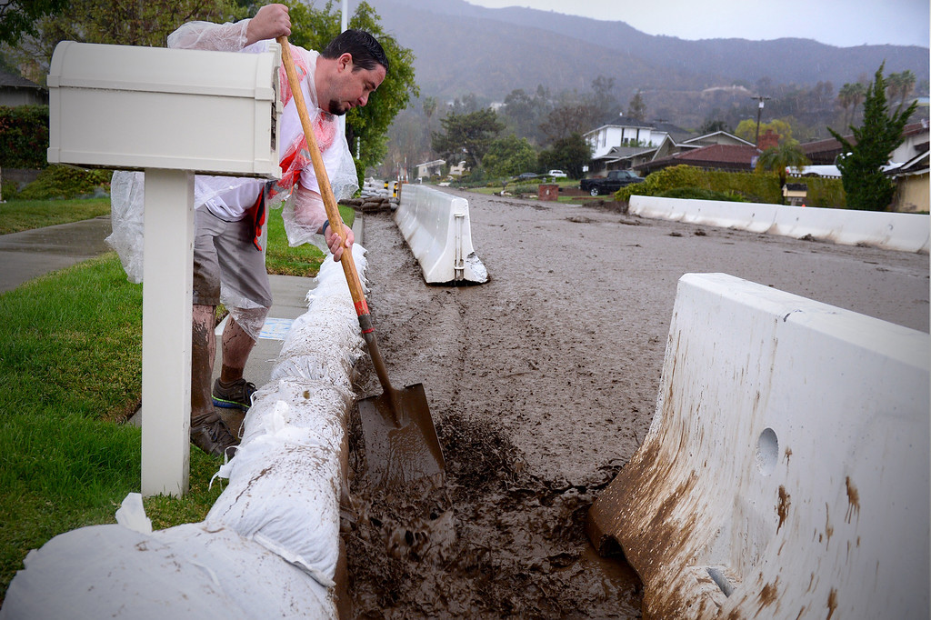 Description of . A neighbor helps clear storm drains on Rainbow Drive in Glendora as the rainstorm starts up again Saturday afternoon, March 1, 2014. The neighborhood sits below the Colby Fire burn area. Resident Tom Tice said this was the most water and mud he's seen in three days of the storm. (Photo by Sarah Reingewirtz/Pasadena Star-News)