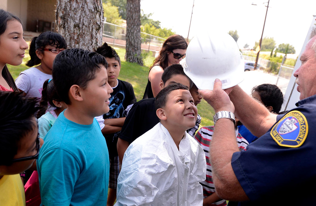 Description of . Brian Otter of San Bernardino County Fire/ Hazardous Material, right,  outfits fourth grader Donovan Barajas with a helmet during the final day of the 19th Annual Career Awareness Week at Lankershim Elementary School in Highland June 6, 2013.  GABRIEL LUIS ACOSTA/STAFF PHOTOGRAPHER.