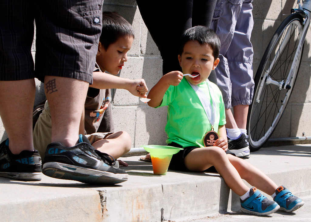 Description of . Arthur Zavala, 3, enjoys shaved ice after placing third in his race at the Redlands Bicycle Classic on Saturday, April 5, 2014 in Redlands, Ca. (Photo by Micah Escamilla for the Redlands Daily Facts)