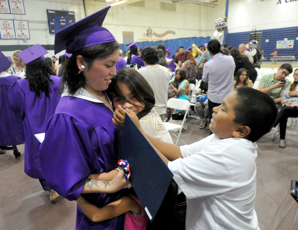 Description of . Melissa Gonzalez is hugged by her nieces and nephew after the Rowland Adult and Community Education Graduation Ceremony at Rowland High School in Rowland Heights on Tuesday June 4, 2013. The 18 graduates and one special recipient received their honors in front of their families in the Gym. (SGVN/Staff Photo by Keith Durflinger)