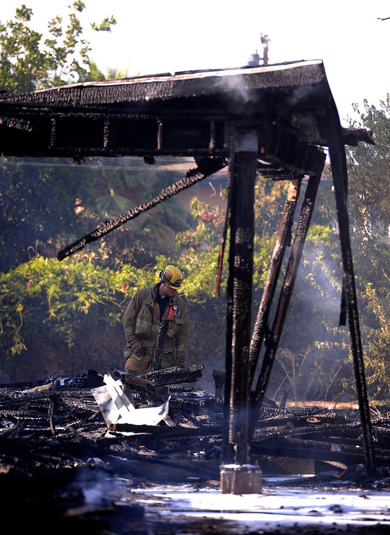 Description of . A firefighter looks at a vacant home that was destroyed by a four-alarm fire along the 700 block of Seventh Street in San Bernardino August 18, 2013. GABRIEL LUIS ACOSTA/STAFF PHOTOGRAPHER.