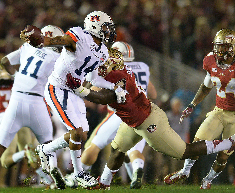Description of . Auburn QB Nick Marshall tries to avoid Florida State's Mario Edwards Jr. in the first quarter of the BCS national championship game at the Rose Bowl, Monday, January 6, 2014. (Photo by Michael Owen Baker/L.A. Daily News)