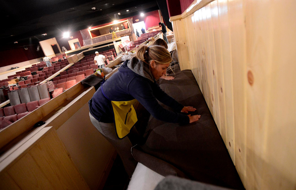Description of . Danielle Loper works on upholstering bench seating in The Cave Theater in Big Bear Lake May 6, 2013.  The music venue, which was originally a movie theater, is set for a grand re-opening for June 7.  GABRIEL LUIS ACOSTA/STAFF PHOTOGRAPHER.
