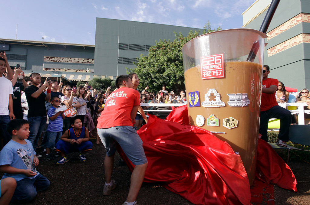 Description of . Albert Chu, 24, and Patricia Huang, 26, unveil the world's largest boba cup, holding approximately 320 gallons of tea, at the 626 night market at Santa Anita Park in Arcadia, Saturday August 3, 2013. (SGVN/Correspondent Photo by Ron Fu/SVCITY)