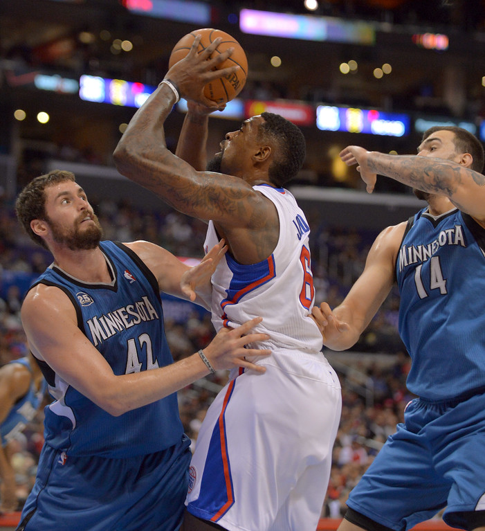 Description of . Los Angeles Clippers' DeAndre Jordan battles under the hoop wth Kevin Love of the Minnesota Timberwolves' in the first half Monday, Nov. 11, 2013, in Los Angeles.(Andy Holzman/Los Angeles Daily News)
