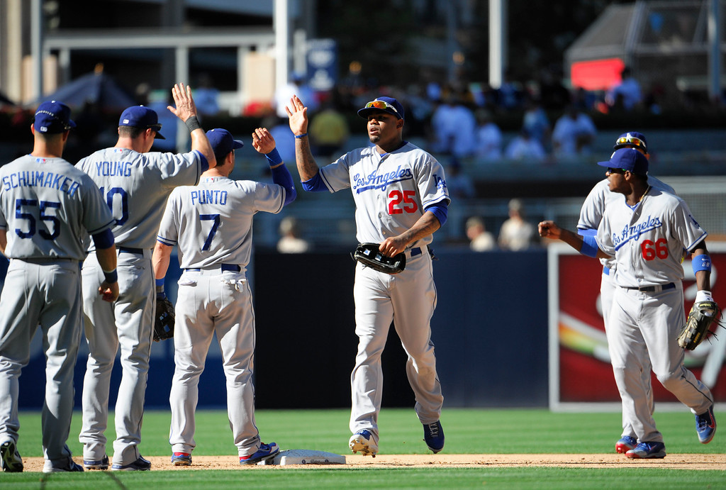 Description of . Los Angeles Dodgers players high-five after beating the San Diego Padres 1-0 in a baseball game at Petco Park on September 22, 2013 in San Diego, California.   (Photo by Denis Poroy/Getty Images)